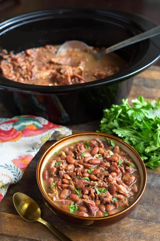 Pinto Beans and Ham in bowl with brown rim in front of slow cooker