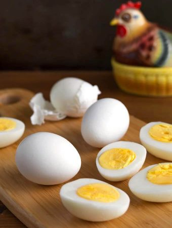 Air Fryer Boiled Eggs on wooden board in front of ceramic chicken