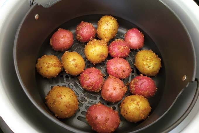 placing potatoes in air fryer basket