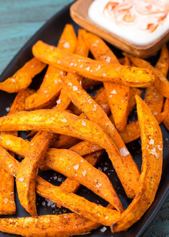 Air Fryer Sweet Potato Fries on black plate with dipping sauce