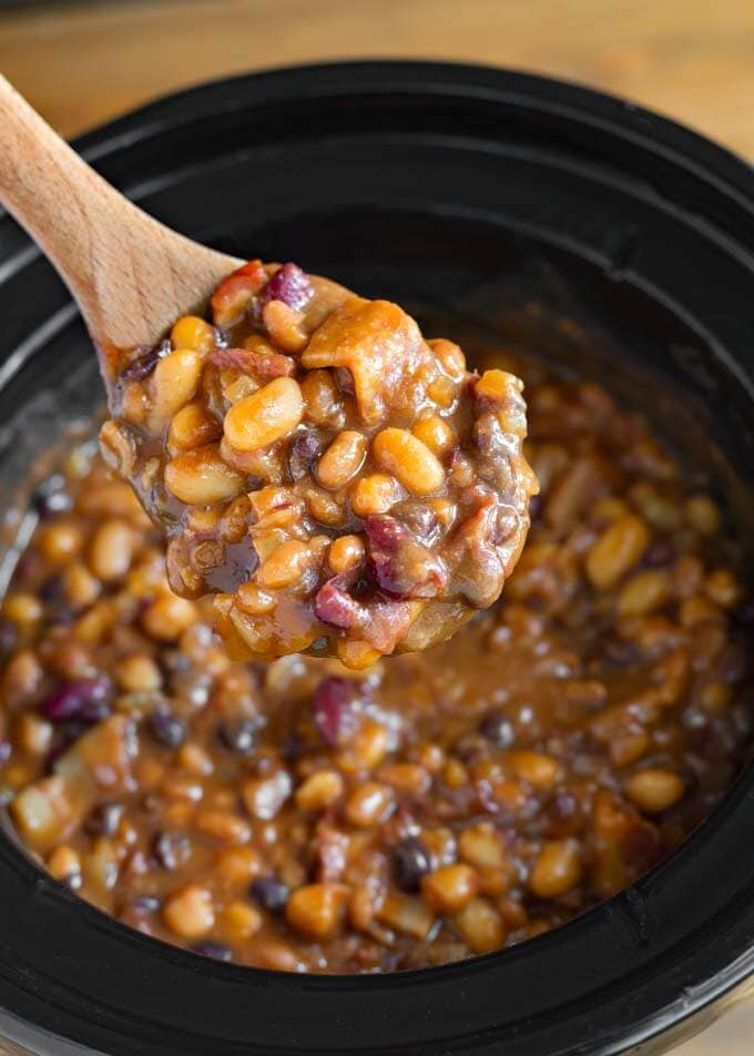 Close up of Baked Beans on wooden mixing spoon over slow cooker
