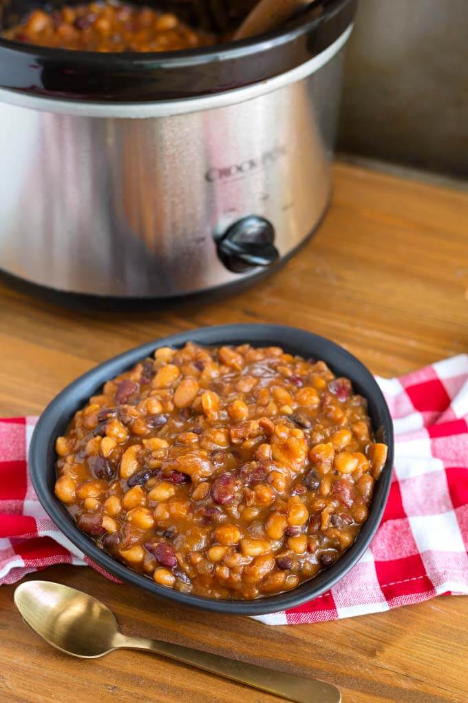 Baked Beans in black bowl on red gingham napkin in front of pressure cooker