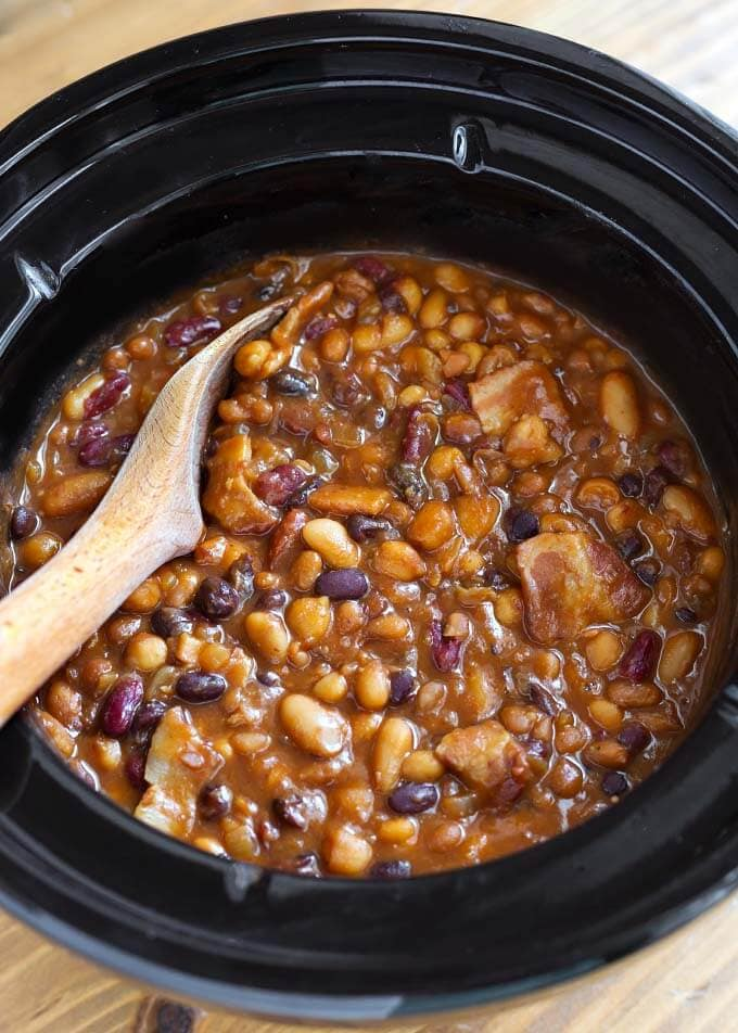 Baked Beans in slow cooker with wooden mixing spoon