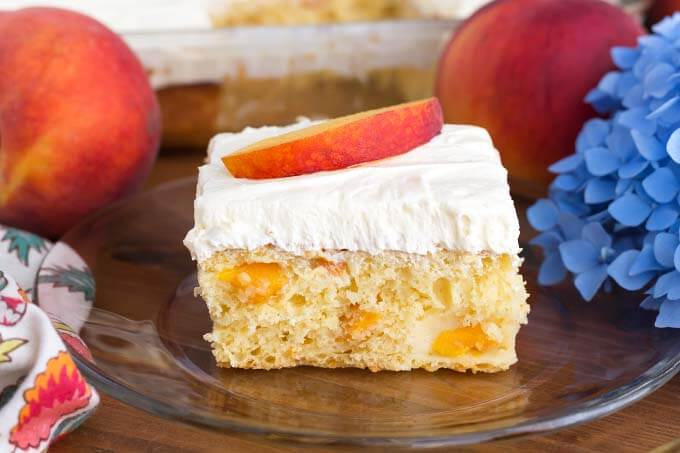 Slice of Easy Peach Potluck Cake on glass plate in front of rest of cake