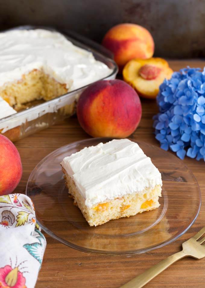 Easy Peach Potluck Cake on glass plate in front of peaches and rest of cake