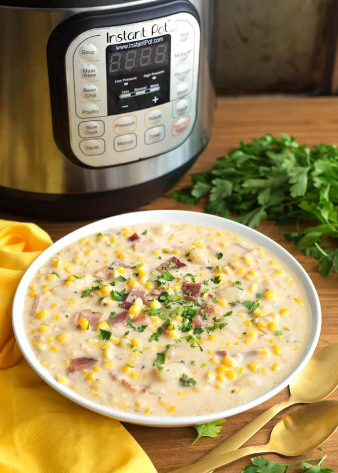 Corn Chowder in white bowl in front of pressure cooker