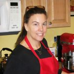 Sandy wearing a black shirt and a red apron