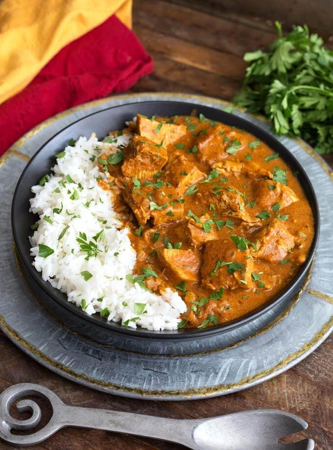 Slow Cooker Indian Butter Chicken with rice on black plate on top of silver platter