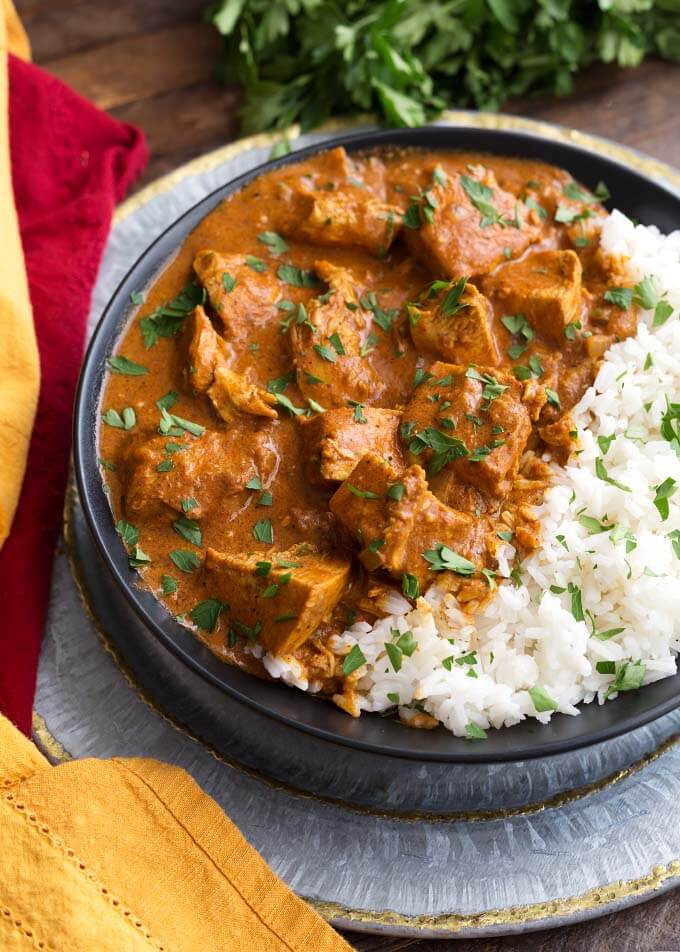 Indian Butter Chicken with rice on a black plate