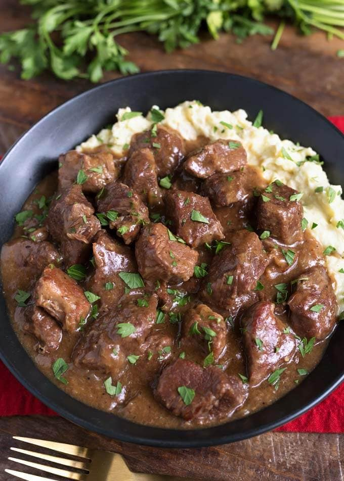 Beef Tips with mashed potatoes in a black bowl