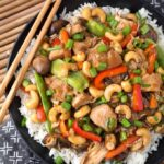 Cashew Chicken over rice on black plate with wooden chopsticks