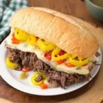 Italian Beef hoagie on white plate on wooden board