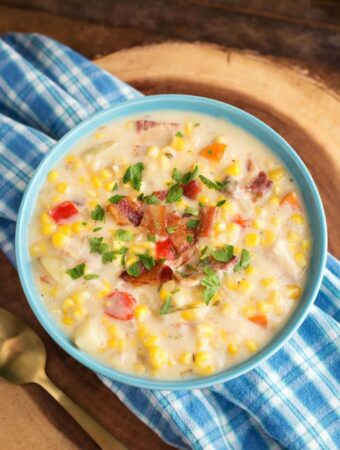 Slow Cooker Corn Chowder in a light blue bowl on blue plaid napkin