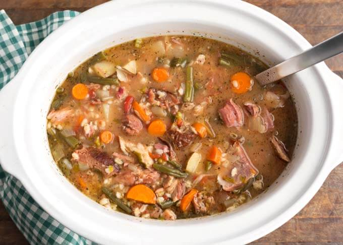 Ham Vegetable Barley Soup in white slow cooker with ladle