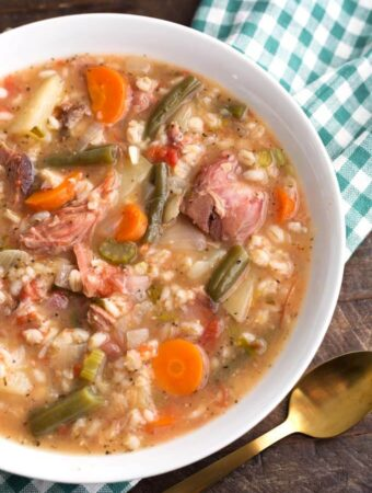 Slow Cooker Ham Vegetable Barley Soup in white bowl on top of green gingham napkin