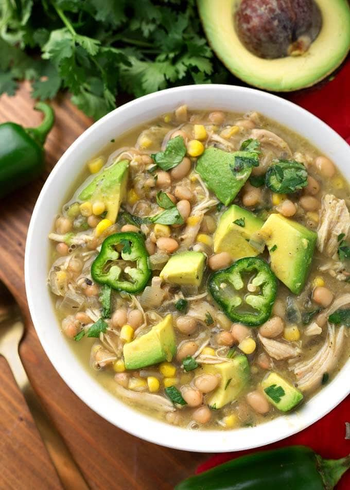 White Chicken Chili topped with diced avocado and fresh jalapeno slices in a white bowl on a wooden board