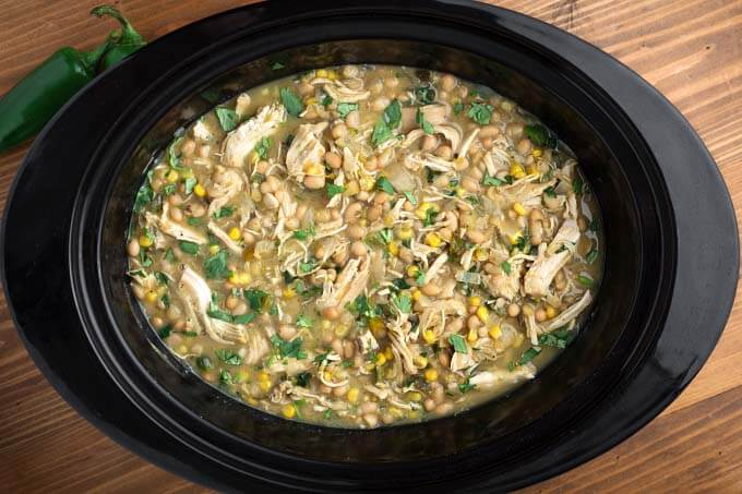 top view of White Chicken Chili in a black slow cooker