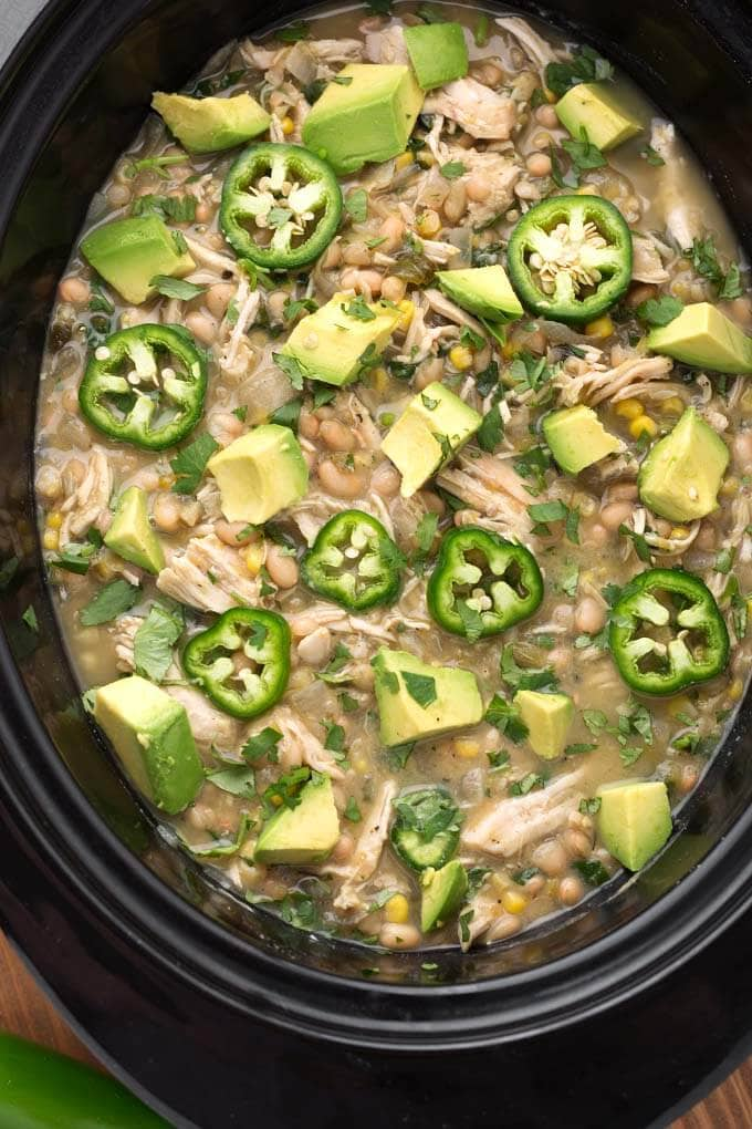 Closeup of White Chicken Chili topped with diced avocado and fresh jalapeno slices in a black slow cooker