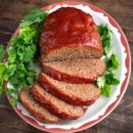 Easy Slow Cooker Meatloaf on a white plate garnished with parsley