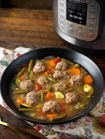 Pressure Cooker Albondigas Soup in black bowl in front of pressure cooker