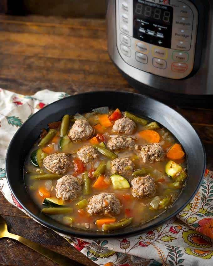 Pressure Cooker Albondigas Soup in black bowl in front of pressure cooker