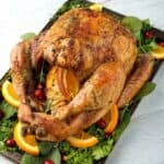 Thanksgiving Turkey on baking sheet with vegetables, herbs, sliced oranges and cranberries