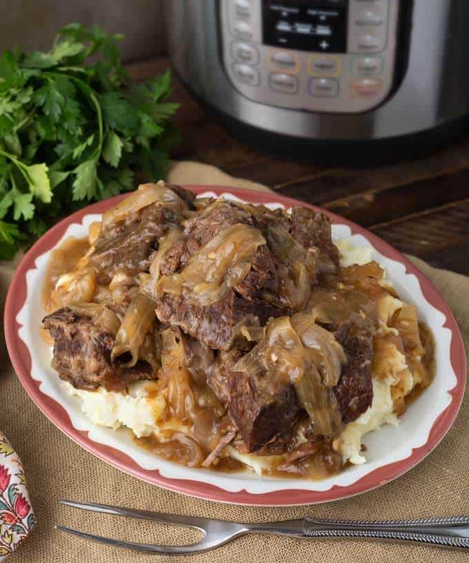 Pressure Cooker French Onion Pot Roast over mashed potatoes on white plate
