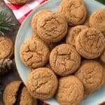 Several Soft Chewy Ginger Cookies on grey plate with red gingham napkin and pine needles in background
