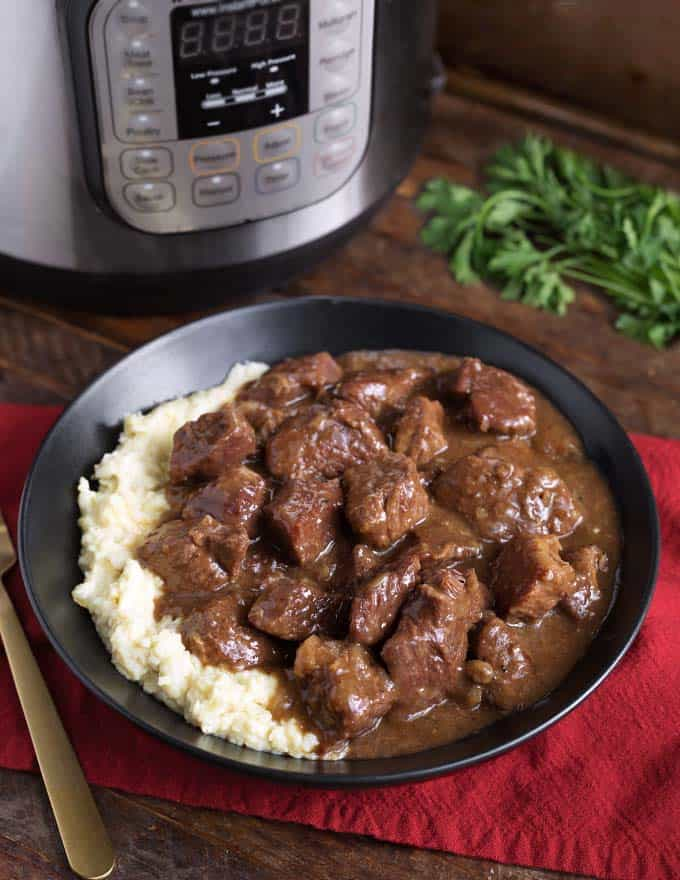 Instant Pot Beef Tips and mashed potatoes in a black bowl in front of pressure cooker