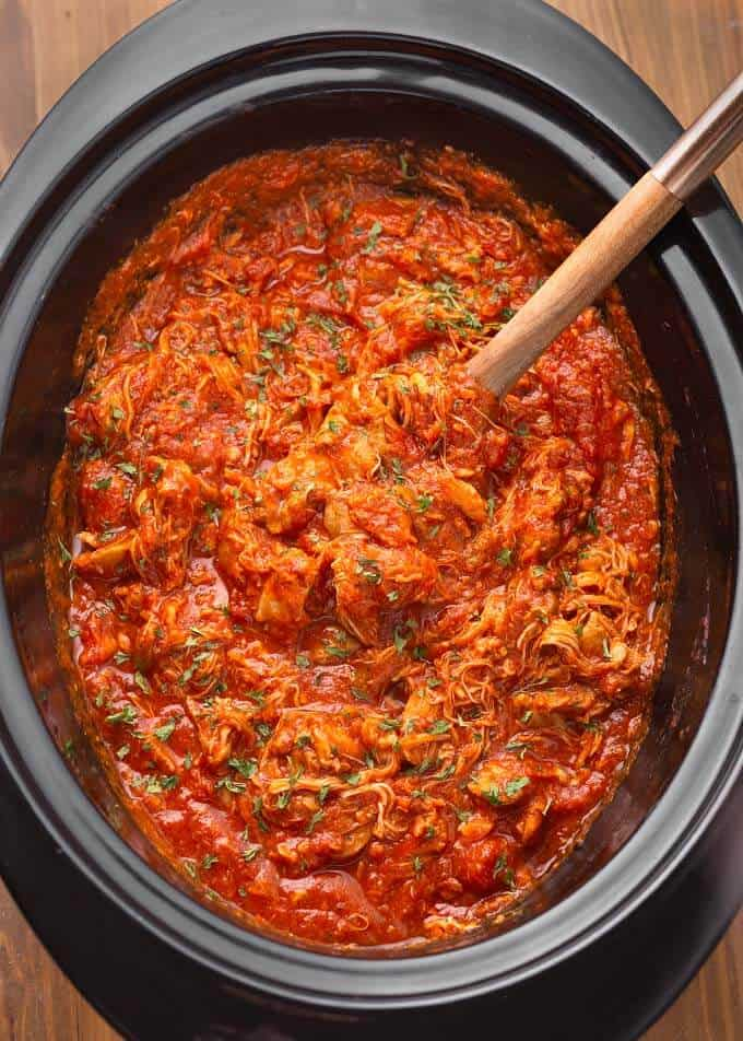 Chicken Cacciatore in slow cooker with wooden mixing spoon