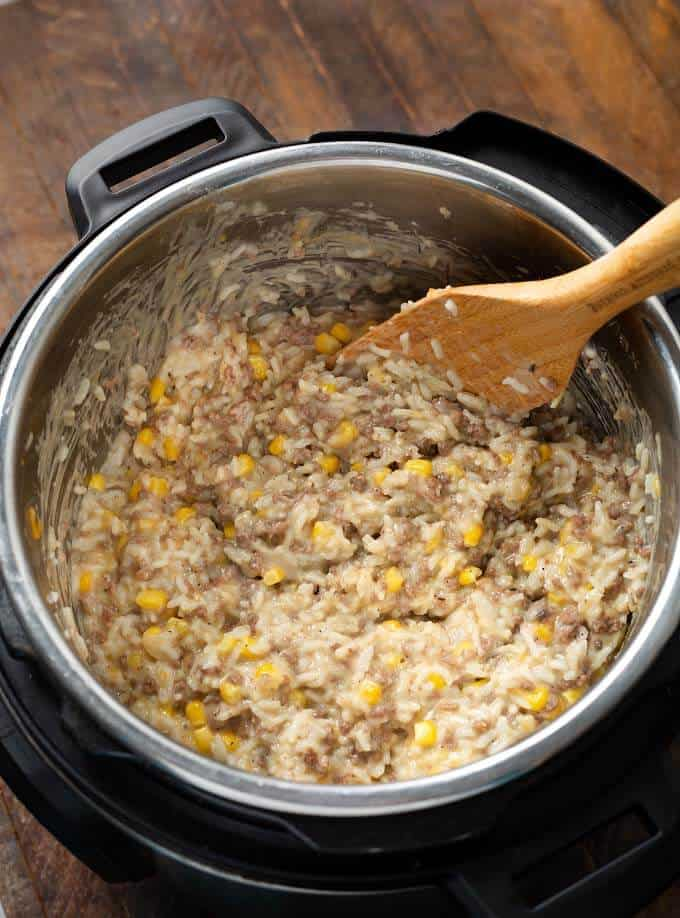 Cheesy Hamburger Rice Casserole in pressure cooker pot with wooden spoon