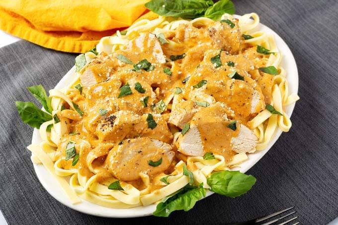 Sliced Pressure cooker Creamy Cajun Chicken Breast over noodles on oval plate