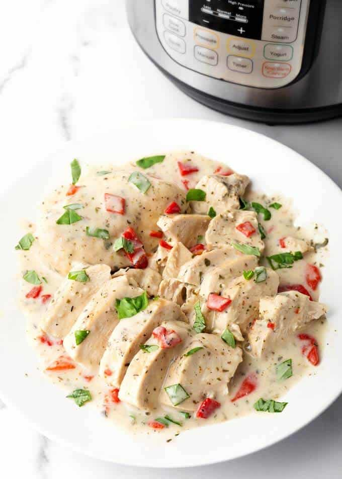 Sliced Pressure cooker Creamy Italian Chicken Breasts on a white plate