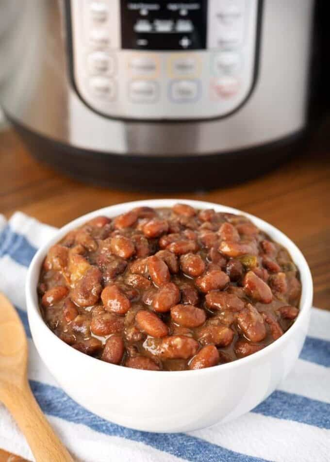 Pressure cooker Mexican Pinto Beansin white bowl in front of pressure cooker