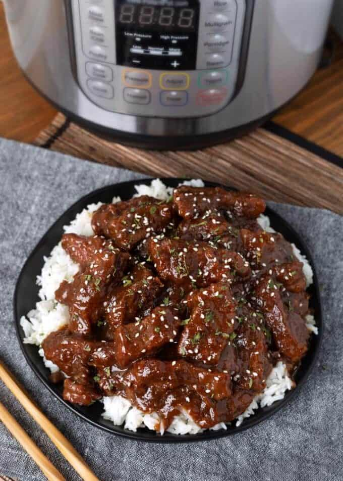 Pressure Cooker Mongolian Beef over rice on black plate next to wooden chopsticks