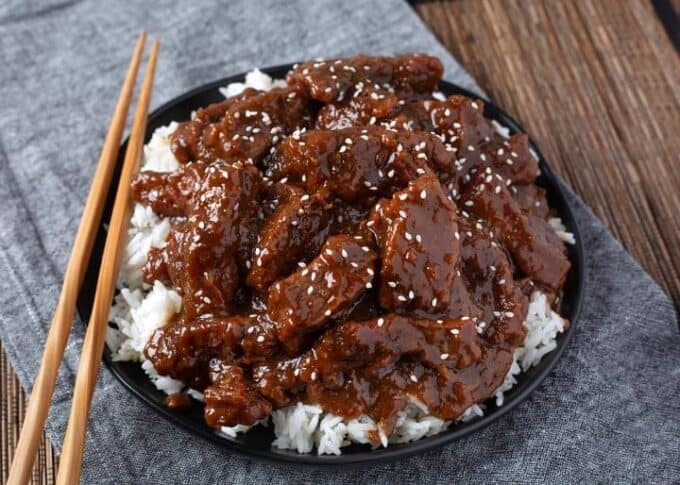 Pressure cooker Mongolian Beef over white rice on black plate with wooden chopsticks