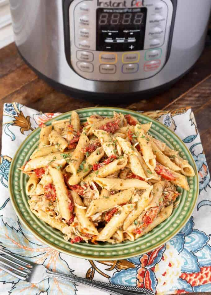 Pressure cooker Pesto Pasta on green plate in front of pressure cooker