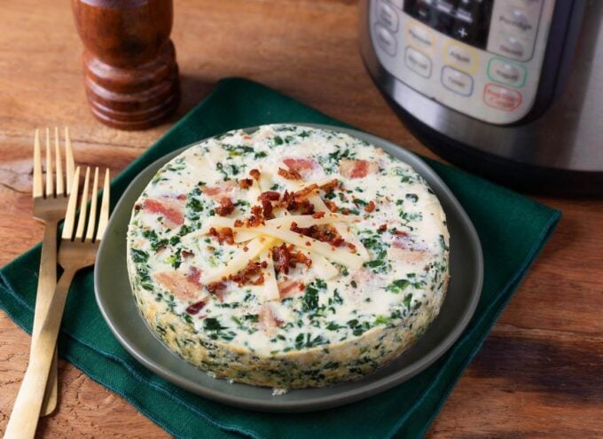whole pressure cooker Spinach Bacon Crustless Quiche on a plate next to two forks