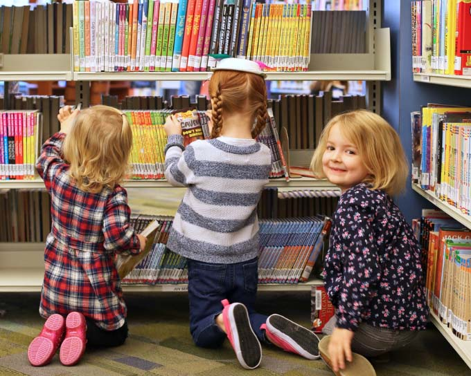 three young girls looking for books at a library