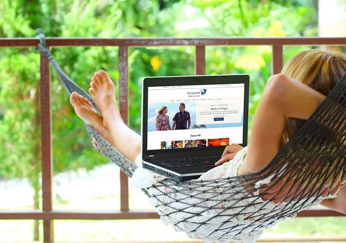 woman in hammock looking at laptop computer