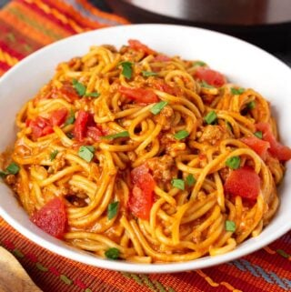 Taco Spaghetti in a white bowl on a red orange striped cloth