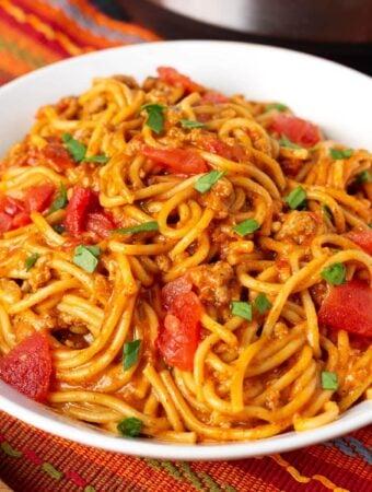 Taco Spaghetti in a white bowl on a red orange striped cloth