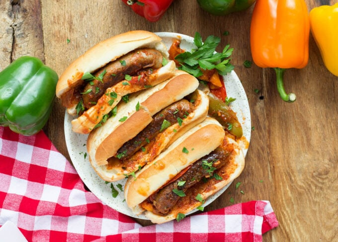 three sausage and peppers on hoagie rolls on a white plate on a wood background