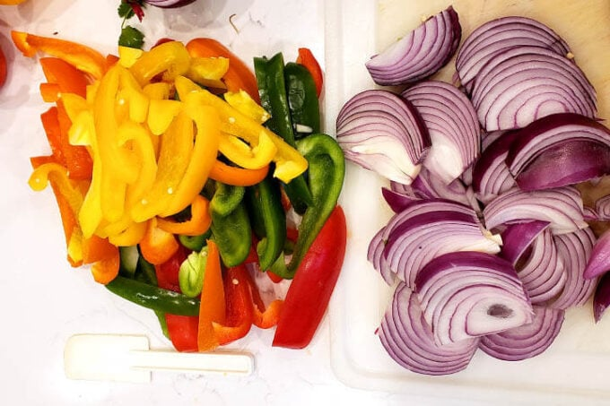 sliced bell peppers and red onion on a white cutting board from above