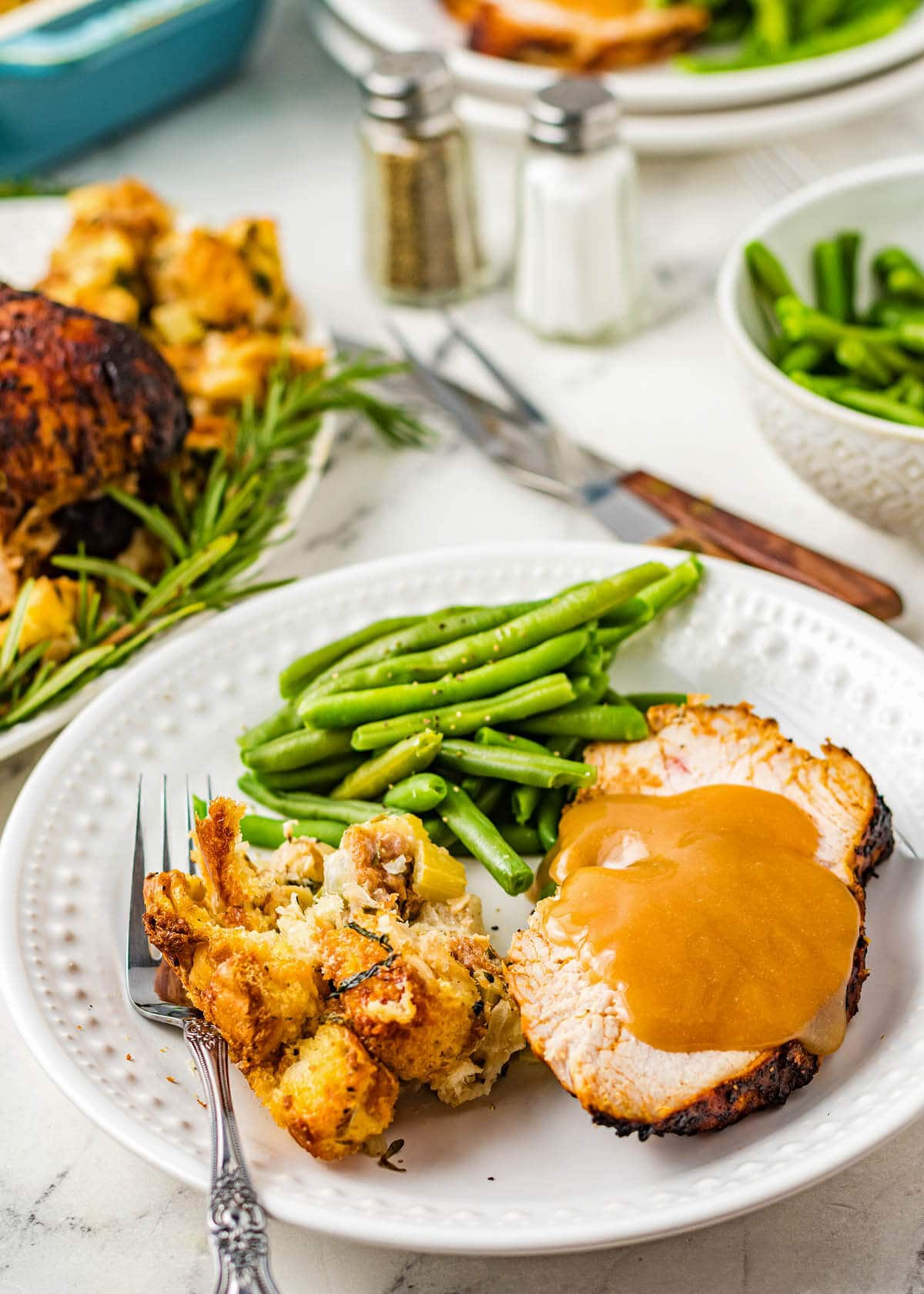 Air Fryer Turkey Breast slice on a white plate with beans and stuffing