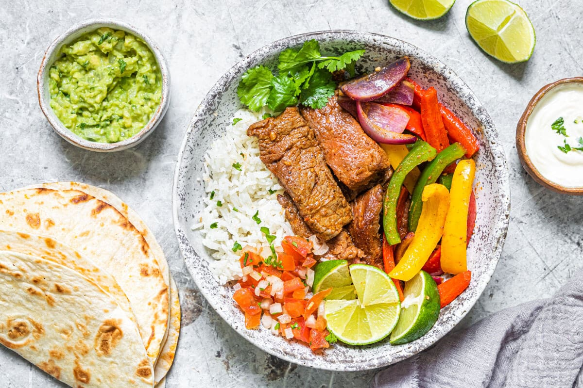 Air Fryer Fajitas with tortillas and garnishes on a grey plate